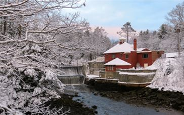 A house near a river in a wooded area all covered by snow